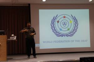 Hasan Dikyuva, board member of the World Federation of the Deaf, gives the opening speech