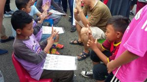 A deaf Indonesian boy teaches a hearing peer how to fingerspell in BISINDO